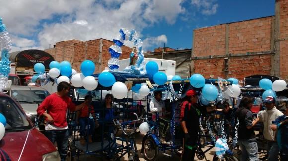 …en un entorno festivo, abarrotado de los ya famosos ciclo-taxis de la zona, cuidadosamente adornados de vistosos globos con los colores de la Virgen María.