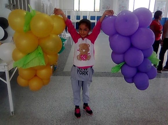 """… y, niñas, a fin de cuentas, terminada la Misa, descubren, divertidas, los racimos de uvas gigantes que estaban preparados para alguna fiesta y no resisten la tentación de jugar con ellos. Como ya os habréis dado cuenta, aquí en Colombia, los globos o """"balones"""", como ellos los llaman, son el adorno fundamental de toda celebración."""